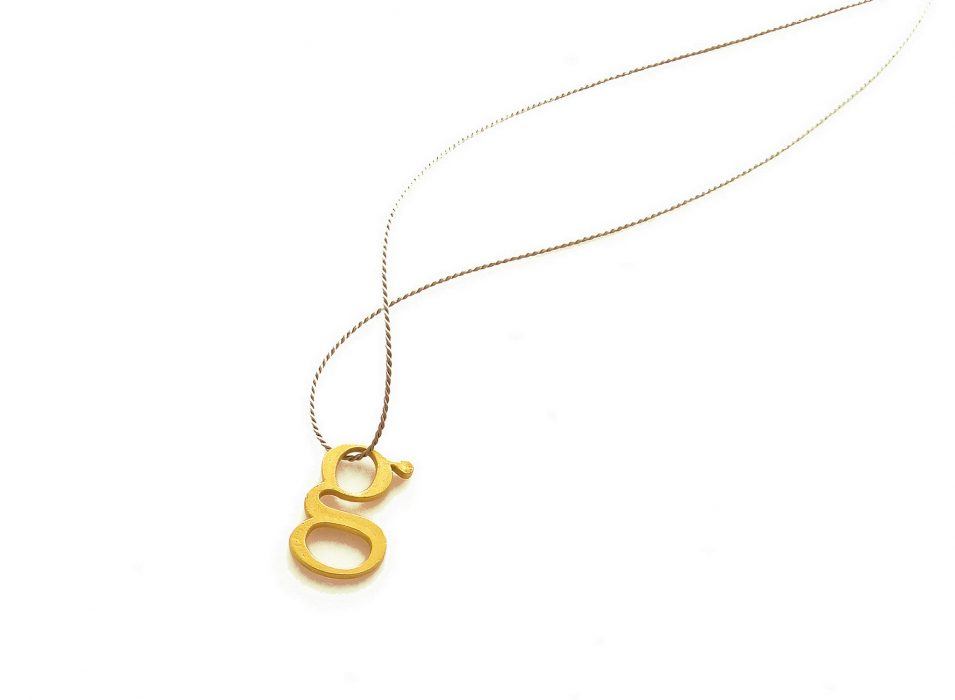 "< 1g gold >, necklace, material: 18K gold, silk string. 1 ""g"" weights exactly 1 gram."